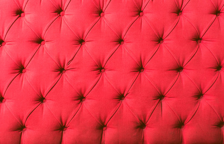 pink upholstered textile backdrop with symmetric buttons