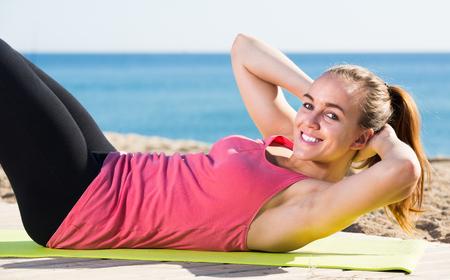 Smiling young woman doing  gymnastics exercises at sea beach