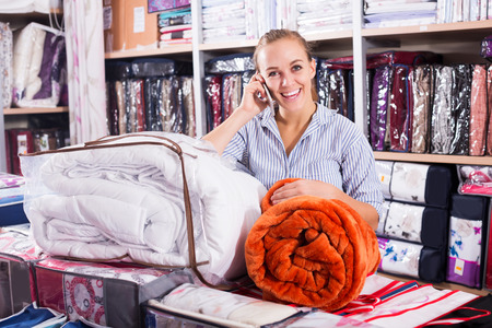 coverlet: Positive young woman enjoying her new blanket and coverlet in textile shop