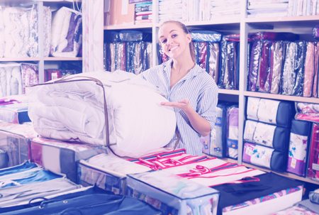 coverlet: Young female customer buying new blanket and coverlet in textile shop
