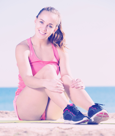 Positive adult sporty woman exercising at sea beach