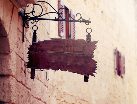 shopsign: old wooden  plaque on wall old mediterranean street