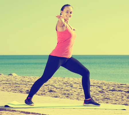 concentrated girl exercising on exercise mat outdoor at the seaside