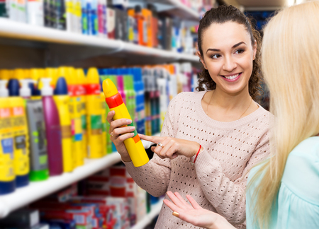 Portrait two cheerful women choosing hair styiling mousse and smiling Stock Photo