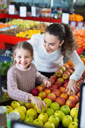 purchasers: Happy smiling mother and little daughter choosing seasonal fruits in grocery Stock Photo
