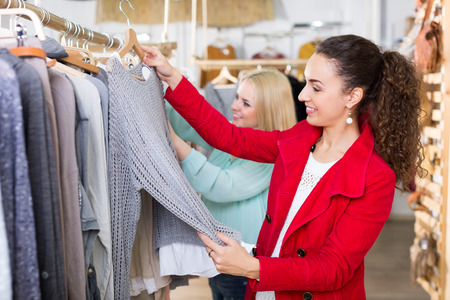 Two positive young women choosing basic garments at clothing store