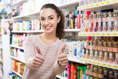 eau de perfume: Portrait of lovely young brunette shopping in a beauty store