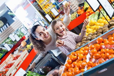 purchasers: Cheerful positive smiling mother and little girl choosing fresh fruits in grocery Stock Photo