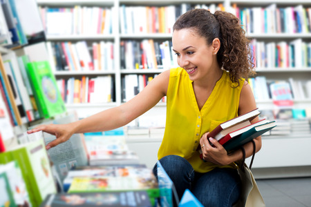 Beautiful glad woman taking literature books in store with prints Stok Fotoğraf