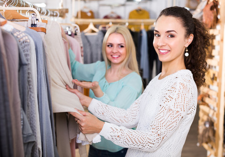 Two smiling girls selecting basic garments at clothing store