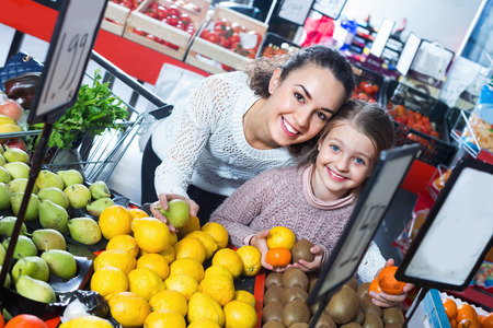 purchasers: Cheerful smiling mother and little girl choosing fresh fruits in grocery