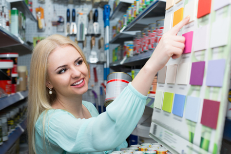 25s: Happy woman choosing decorating paint in household section of supermarket
