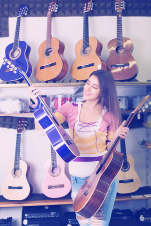 happines: Happy young female customer buying new guitar in store and smiling Stock Photo