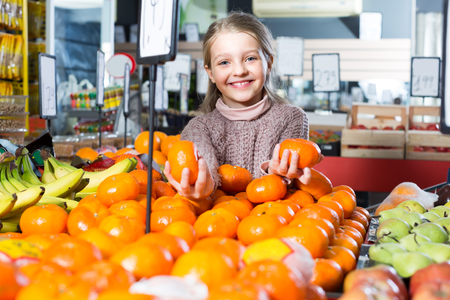 purchasers: Portrait of cute smiling little girl selecting ripe tangerines at market