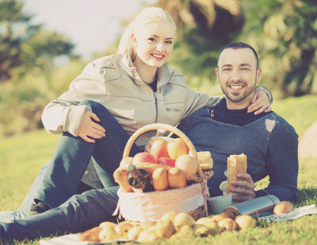 sandwitch: Loving cheerful young couple chatting as having picnic in sunny day