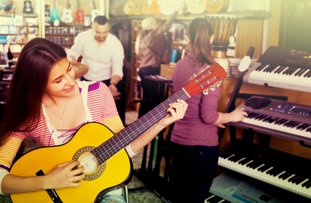 Smiling people looking at professional musical instruments in store Stock Photo
