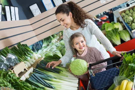 purchasers: Happy positive mother with smiling small daughter buying fresh celery and cabbage