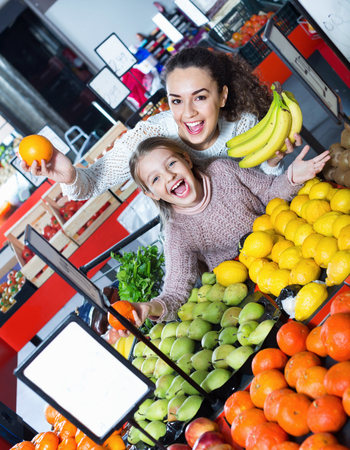 Cheerful mother and smiling little girl choosing fresh fruits in grocery Stock Photo