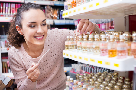 lustre: Happy young woman choosing things for makeup and smiling at a store Stock Photo