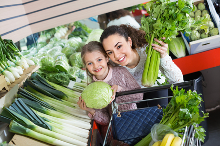 Young positive female and cheerful smiling little girl shopping green veggies in grocery