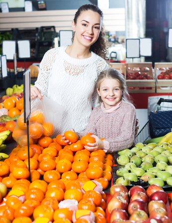 Brunette smiling woman and happy daughter purchasing fruits and smiling in store