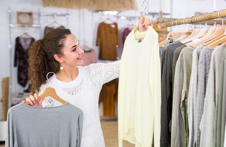 Brunette female customer selecting basic garments at the store