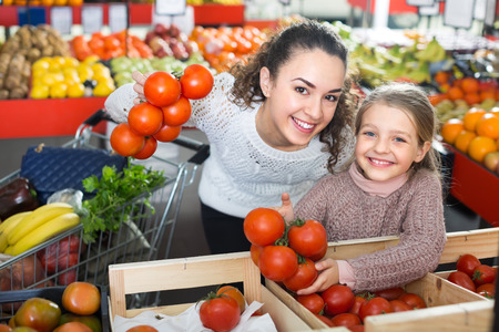 purchasers: Cheerful smiling young woman with little daughter buying  globe tomatoes at  the market