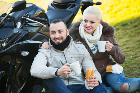 25s: Positive couple having picnic with coffee near cycle