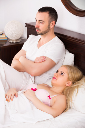Angry woman and man having problems in bed