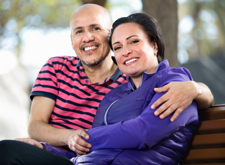 Close-up outdoors portrait of happy smiling man and woman happily embracing each other