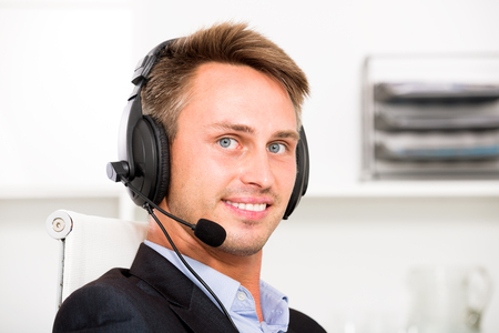 headset voice: Positive young man talking using hands-free set at customer service office