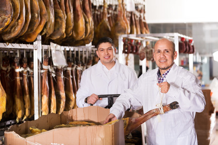 middle joint: Mature butcher and assistant with jamon joints at a meat factory