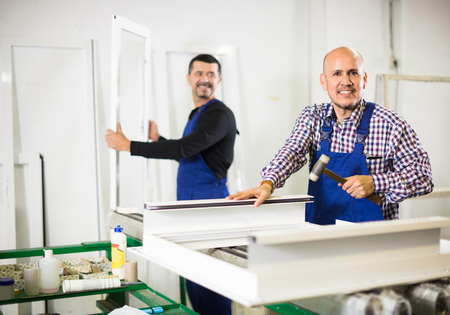 toolroom: Smiling workers in blue coverall with different PVC windows and doors at workshop