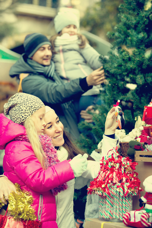 Family with children purchasing the Christmas decoration and souvenirs at a fair. Focus on women Editorial