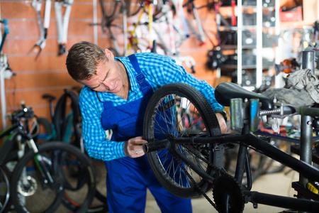 Man seller wearing uniform fixing bike in sport store