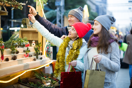 positive european family of three with teenage girl choosing  floral decorations  at market. Shallow depth of focus