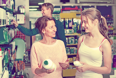 Smiling woman with girl teenager packing body care goods in pharmaceutical store
