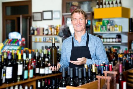 Portrait of positive male seller wearing uniform with wine bottle in hands in wine shop