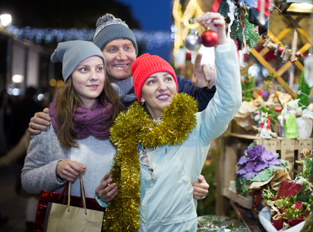 Smiling family walking on the Christmas market and chooses Christmas decorations Editorial
