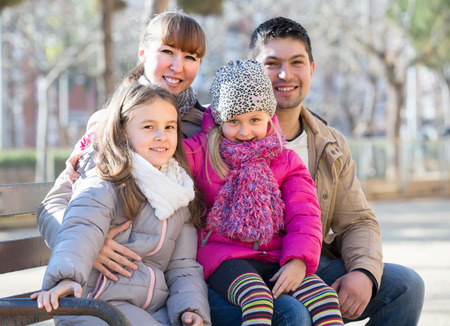 Cheerful young parents with cute little daughters sitting on bench outside. Focus on girl Editorial