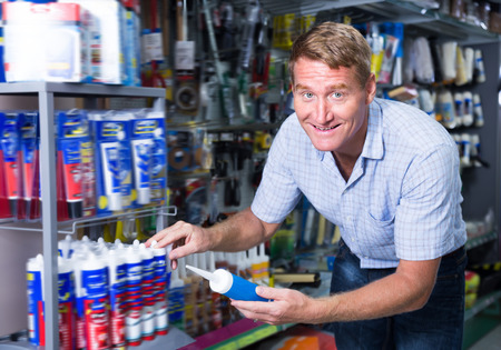 sealant: Glad man customer picking sealing component in household shop Stock Photo