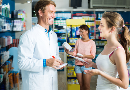 buying questions: Glad man pharmacist wearing white coat helping customers in drug store