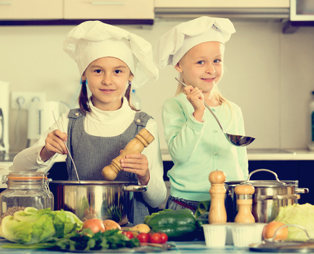 Happy smiling little sisters in caps learning how to cook at home kitchen Stock Photo