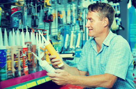 sealant: Cheerful man customer picking sealing component in household shop Stock Photo