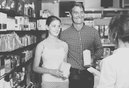 buying questions: portrait of glad european man with daughter teenager shopping medicine in drug store