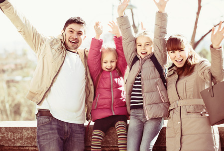 Cheerful mother, father and little girls in city at sunny day