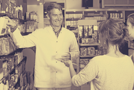 buying questions: cheerful mature male pharmacist in white uniform consulting customers in pharmaceutical shop