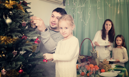 Happy parents with two children decorating Christmas tree and serving table for dinner at home. Focus on girl