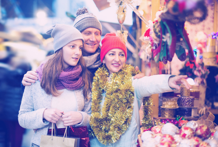 Attractive parents with teenage girl at counter at the Christmas Fair. Shallow depth of focus