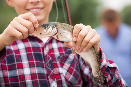 portrait of smiling teenager boy holding catch fish on hook outdoors  . Focus on fish